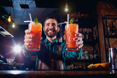 Barman holds out cocktails to client at the bar in restaurant. royalty free stock image