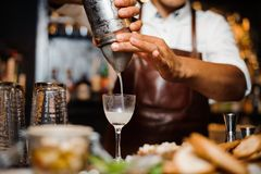 Barman i mixes a white cocktail using bar equipment. Barman in a white shirt and brown apron mixes a white cocktail behind a bar counter using bar equipment Stock Images