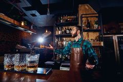 The barman juggler throws up a glass for  cocktail at bar.  Stock Images