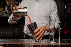 Barman mélangeant dans le dispositif trembleur de cocktail en acier une boisson alcoolisée rouge transparente Photographie stock libre de droits