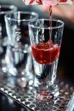 Barman makes shots in a bar Stock Image