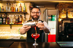 Barman is making alcohol cocktail at counter Stock Images