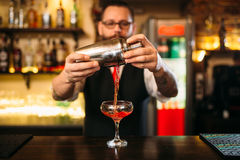 Barman is making alcohol cocktail at counter Royalty Free Stock Image