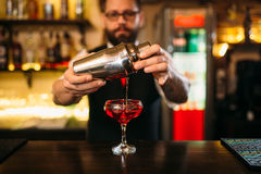 Barman is making alcohol cocktail at counter. Barman is making alcohol cocktail at bar counter. Barman with shaker and glass of beverage stock image