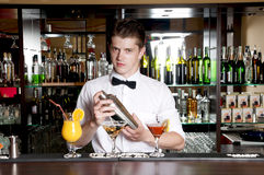 Barman making cocktail drinks. Young handsome barman standing in front of the bar and making cocktail drinks stock images