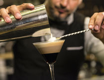 Barman is making cocktail at night club. He is elegant stock photography