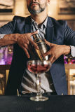 Barman is making cocktail at night club. Royalty Free Stock Photography