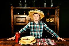 Barman masculin dans un sombrero se tenant au compteur, bouteille de Photographie stock