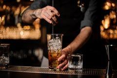 Barman masculin remuant le cocktail d'alcool avec la cuillère de barre images libres de droits