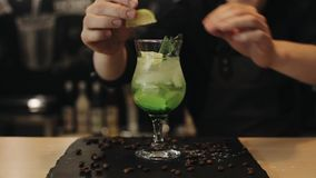 Barman masculino que decora o cocktail do mojito com cal, limão, hortelã Um close-up vídeos de arquivo