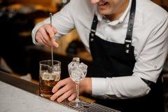 Barman miesza up lód w whisky używać łyżkę zdjęcia royalty free