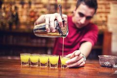 Barman mixing and pouring a summer alcoholic cocktail into small Stock Image