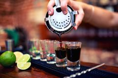Barman mixing and pouring a summer alcoholic cocktail Stock Photos