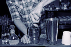 Barman is muddling cocktail ingredients in shaker, toned. Image Royalty Free Stock Images