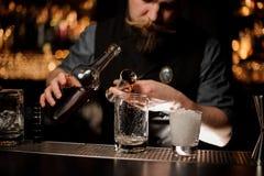 Barman nalewa alkohol koktajl od stalowej osadzarki zdjęcie stock
