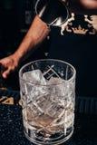 Barman nalewa alkohol w starym mody szkle Obrazy Stock
