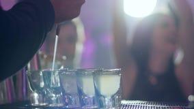 Barman nalewa alkoholicznego koktajl w małych szkła przy baru kontuarem zdjęcie wideo