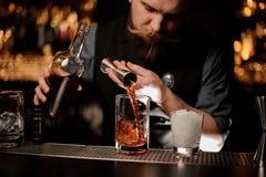 Barman nalewa brązu alkohol koktajl od stalowej osadzarki zdjęcia stock