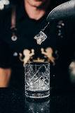 Barman nalewa lód w starym mody szkle Fotografia Royalty Free