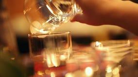 Barman nalewa napój od jeden szkła inny szkło zbiory