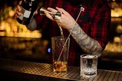 Barman nalewa napój robi Ośniedziałemu gwoździa koktajlowi od stalowej osadzarki pomiarowa filiżanka zdjęcia stock