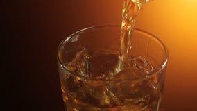 Barman nalewa scotch whisky na skałach, ciepła evening atmosfera, zbiory