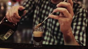 Barman nalewa trzy różnego ciecza i miesza, alkoholiczny koktajl, zakończenie up zbiory wideo