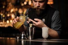 Barman nalewa wyśmienicie alkoholicznego napój od stalowej osadzarki zdjęcie stock