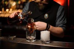 Barman nalewa wyśmienicie brązu koktajl od stalowej osadzarki obrazy stock