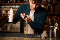 Barman novo que derrama um xarope doce em um vidro Fotografia de Stock Royalty Free
