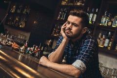 Barman novo que inclina-se no close-up furado contador da barra fotografia de stock