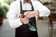 Barman opening bottle with sparkling wine Stock Photos