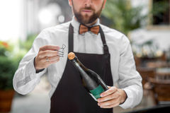 Barman opening bottle with sparkling wine Stock Photography