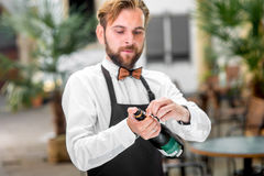 Barman opening bottle with sparkling wine Royalty Free Stock Photo