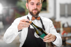 Barman opening bottle with sparkling wine Stock Images