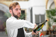 Barman opening bottle with sparkling wine Royalty Free Stock Photography