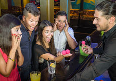 Barman performing magic Trick to surprised Guest. Portrait of a group of people surprised to a barman performing magic tricks Stock Image