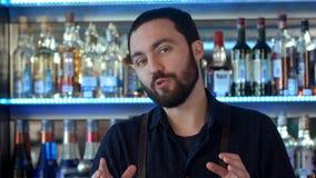 Barman positif parlant à un appareil-photo à un compteur de barre Image stock