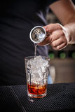 Barman is pouring alcohol Stock Images
