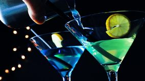 Barman pouring blue and yellow cocktail drink on a disco bar table, disco atmosphere stock video