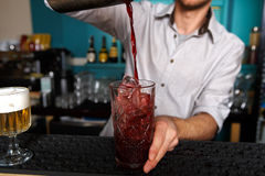 Barman pouring cocktail drink into glass. Barman in bar interior pouring red alcohol to cocktail drink from shaker. Professional bartender at work in night club stock image