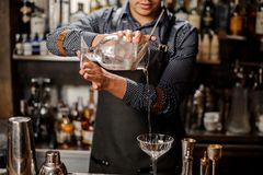 Barman pouring cold alcoholic drink into a cocktail glass Stock Photos