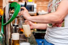 Barman pouring a draught beer at pub or bar Royalty Free Stock Photos