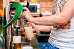 Barman pouring a draught beer at pub or bar Royalty Free Stock Photos