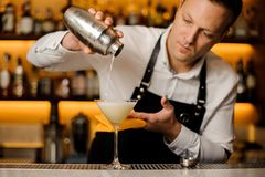 Barman pouring a fresh alcoholic drink into a cocktail glass. Barman pouring a fresh alcoholic drink into an elegant cocktail glass on the bar counter stock photos
