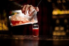 Barman pouring alcoholic tomato cocktail into a glass shot. Barman pouring fresh and salty alcoholic tomato cocktail into a glass shot on the bar counter stock photography