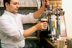 Barman pouring a glass of beer Royalty Free Stock Photo