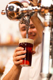 Barman pouring a glass of beer Royalty Free Stock Images