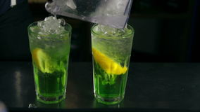 Barman pouring ice and decorating two cocktails with mint. Bartender pouring ice and decorating two cocktails with mint stock video