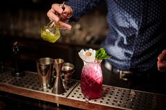 Barman pouring a lime syrup into the glass of sweet strawberry mojito Stock Photos